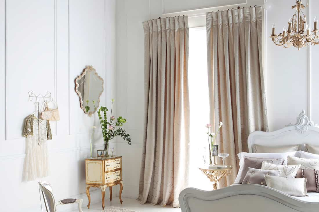 A-womans-bedroom-with-beige-colored-curtains-and-white-walls